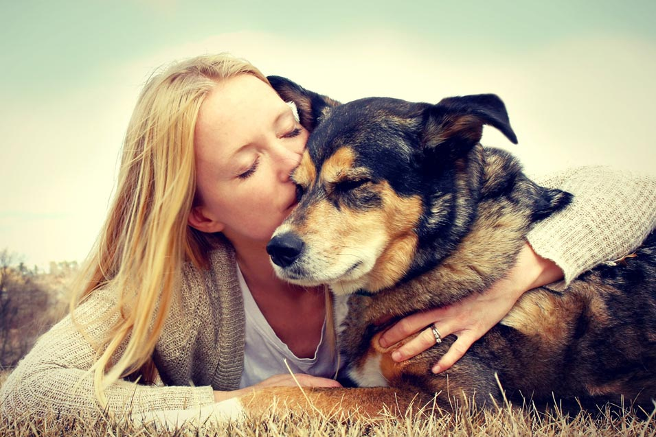 Picture of a woman kissing a old dog
