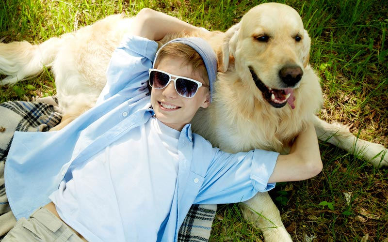 Picture of boy wearing sunglasses and his dog laying on the grass