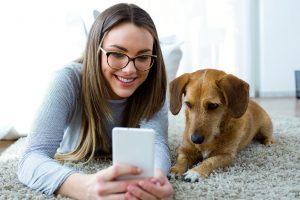 Picture of a dog and girl looking at a iphone