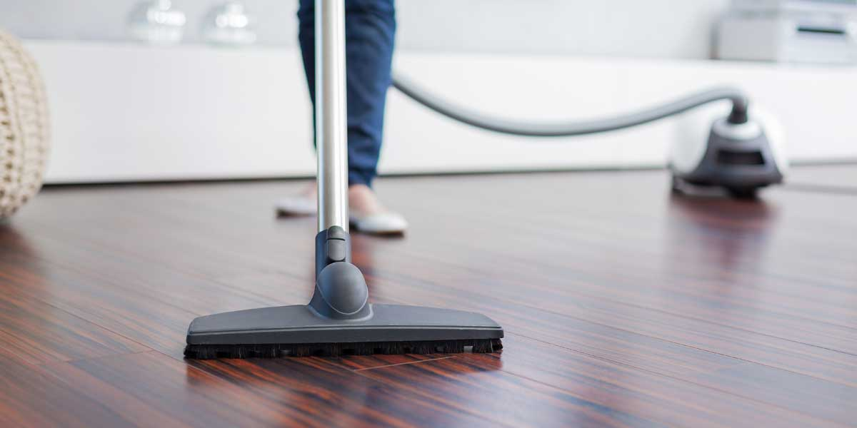 Picture of person vacuuming a hardwood floor