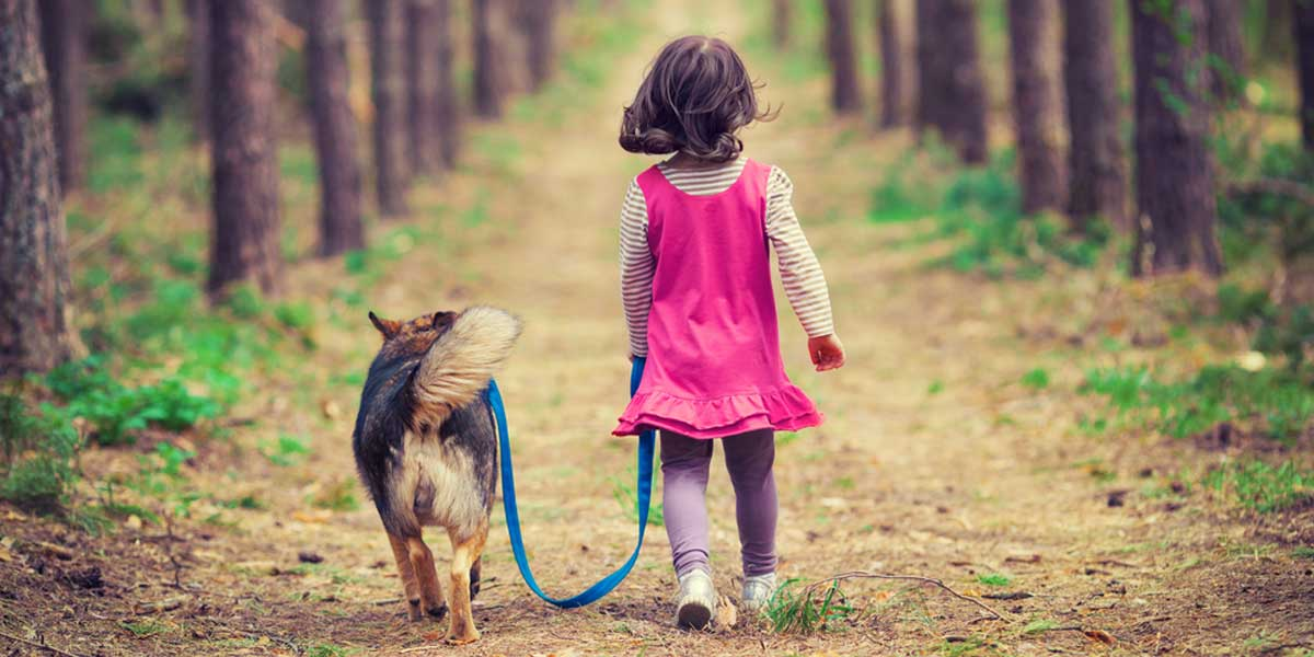 Picture of girl walking a dog down a path