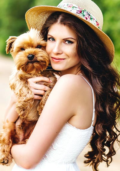 Picture of woman wearing a hat holding a dog
