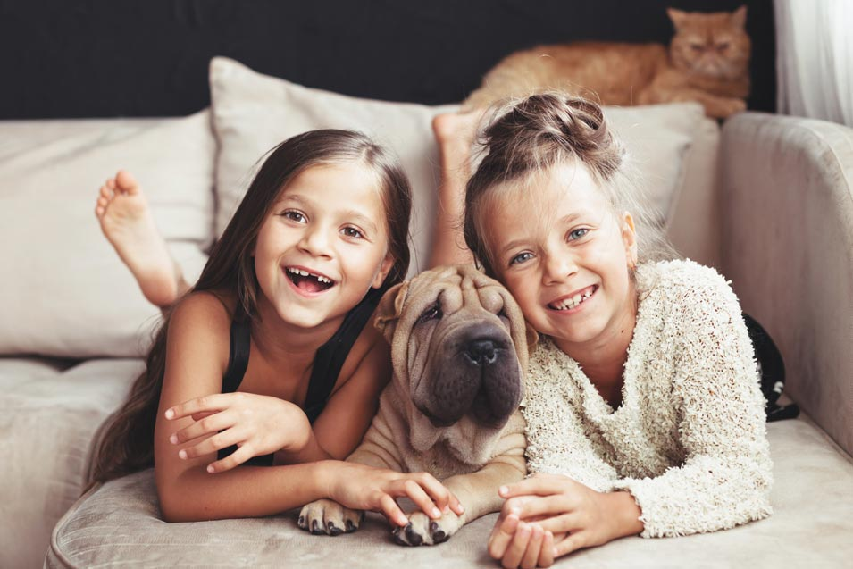 Picture of of 2 girls and a dog laying on the couch