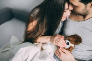 Picture of a couple and their cavalier king charles spaniel puppy