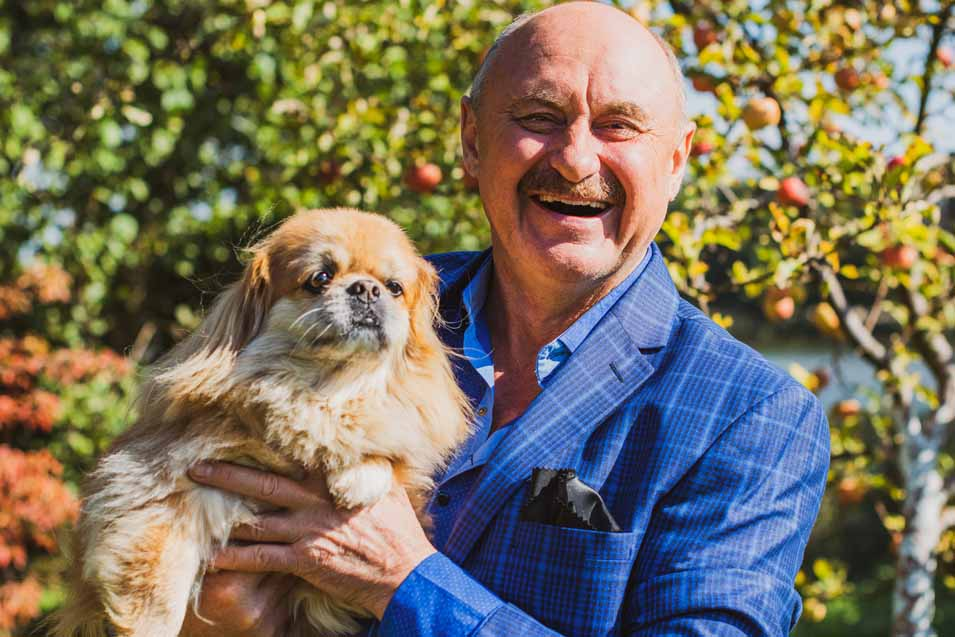 Older man holding a dog
