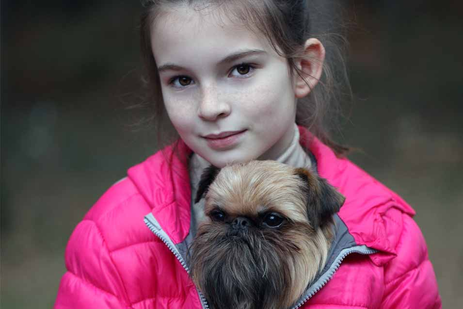 Picture of a Brussels Griffon and a young girl