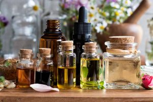 Picture of essential oils, with herbs and flowers in the background