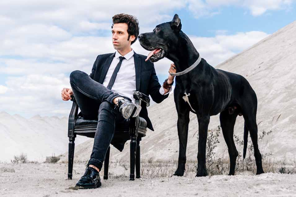 Picture of a Great Dane standing next to a man in a suit