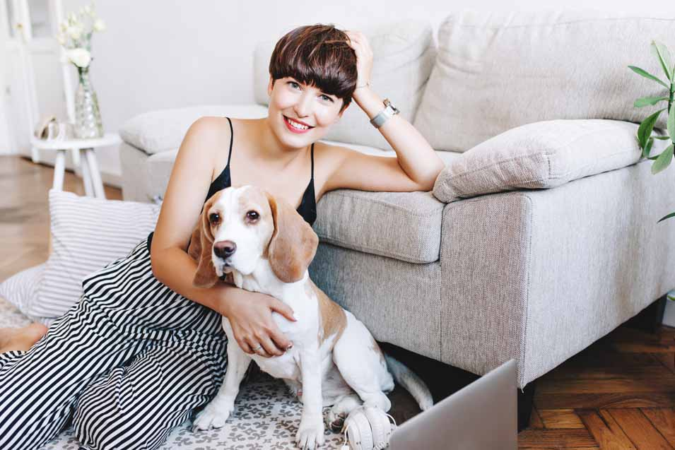 Picture of a woman and dog by a sofa
