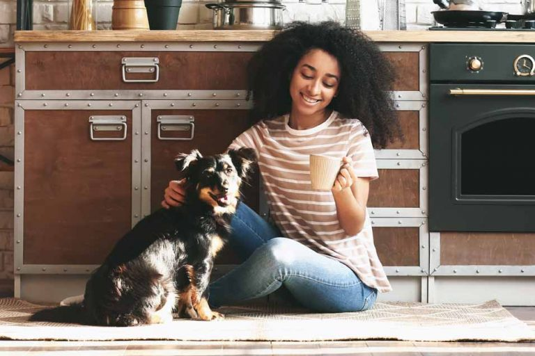 Picture of a girl and dog in the kitchen