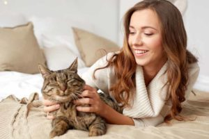 Picture of a woman and a cat on a bed